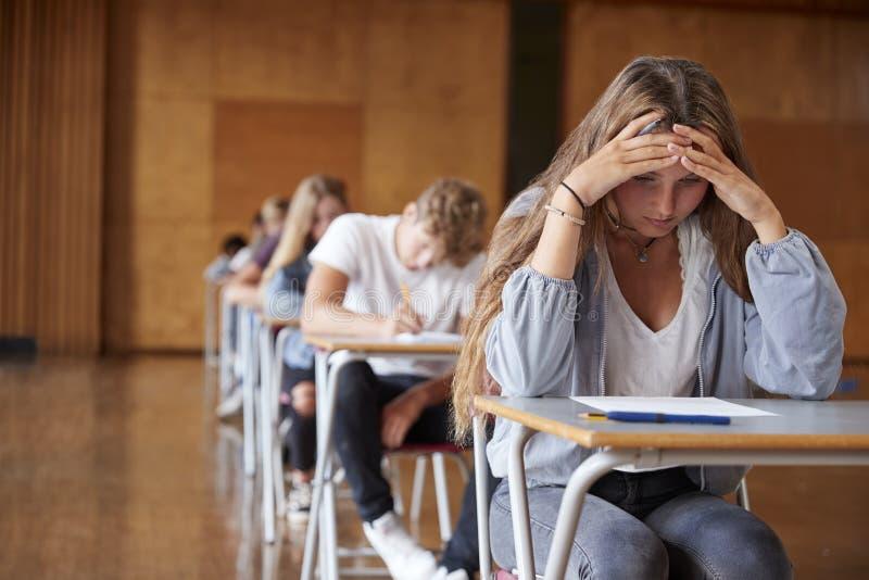 急切少年学生坐的考试在学校霍尔 免版税图库摄影