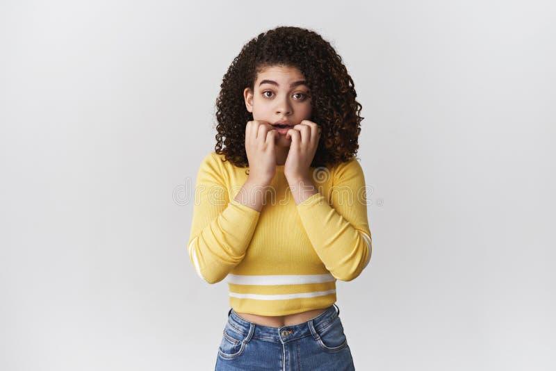 急切缺乏信心的担心的逗人喜爱的强烈的有吸引力的女朋友忧虑咬住的手指凝视看强烈的戏曲电视的照相机 库存图片