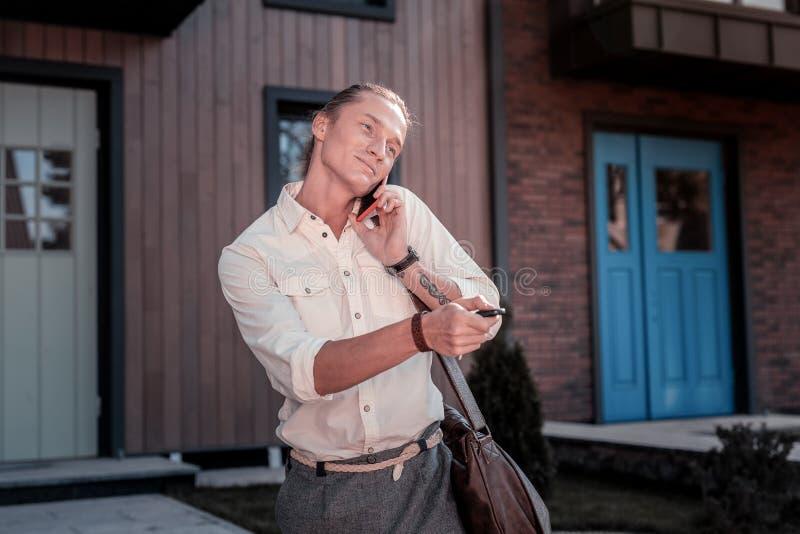 急切要求时间帅哥感觉,当讲话由电话在工作前时 库存照片