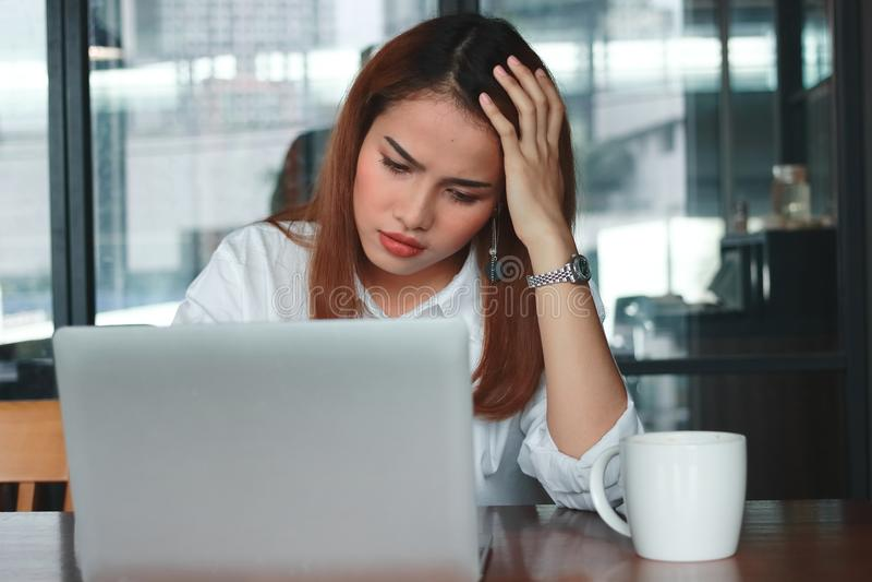 急切遭受严厉的翻倒年轻亚裔女商人正面图从消沉在工作场所 库存图片