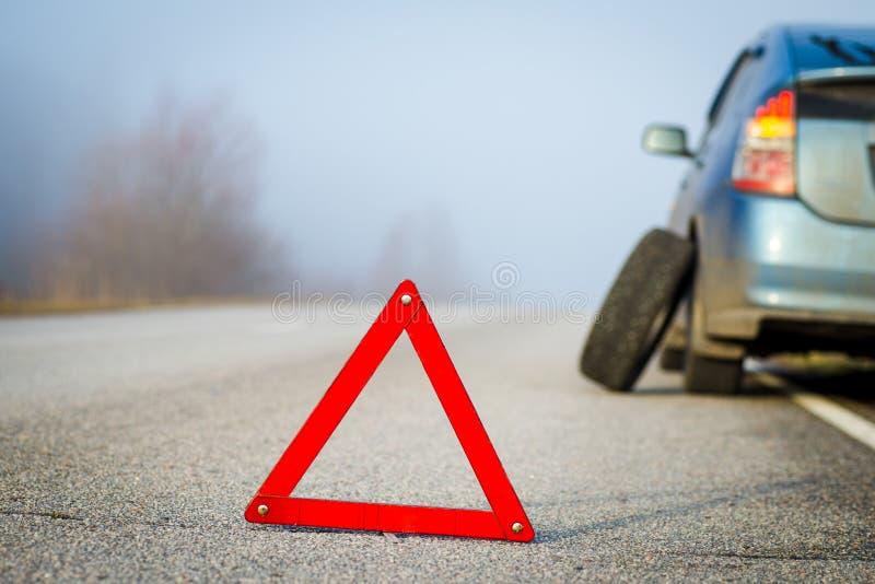 紧急刹车签到与残破的蓝色汽车的背景 免版税库存图片