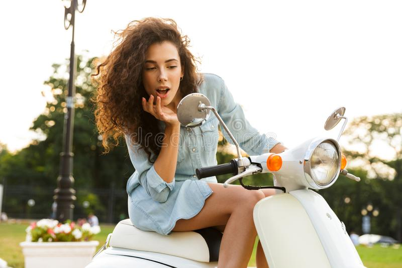 性妇女画象坐时髦的滑行车,当乘坐通过城市街道时 免版税库存照片
