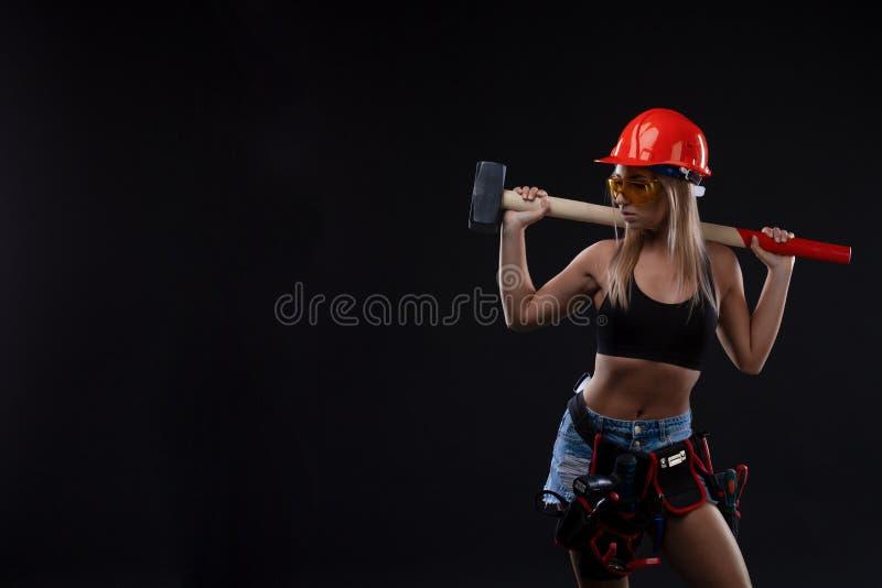 性平等和女权主义 安全橙色盔甲橙色举行的锤子工具的性感的女孩 作为建筑的有吸引力的妇女工作 库存照片