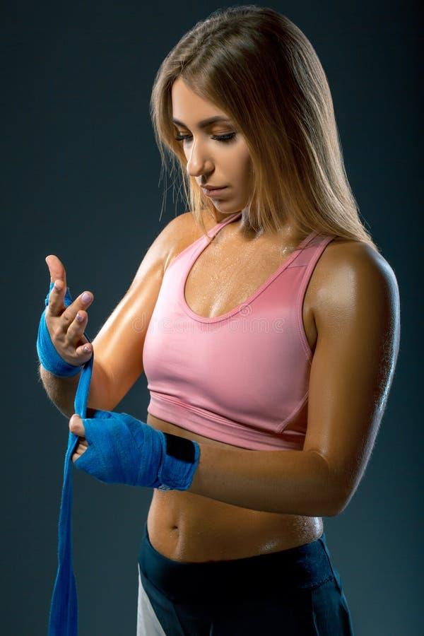 性感和适合的妇女为训练做准备 女孩包裹在她的胳膊的拳击绷带 免版税库存照片