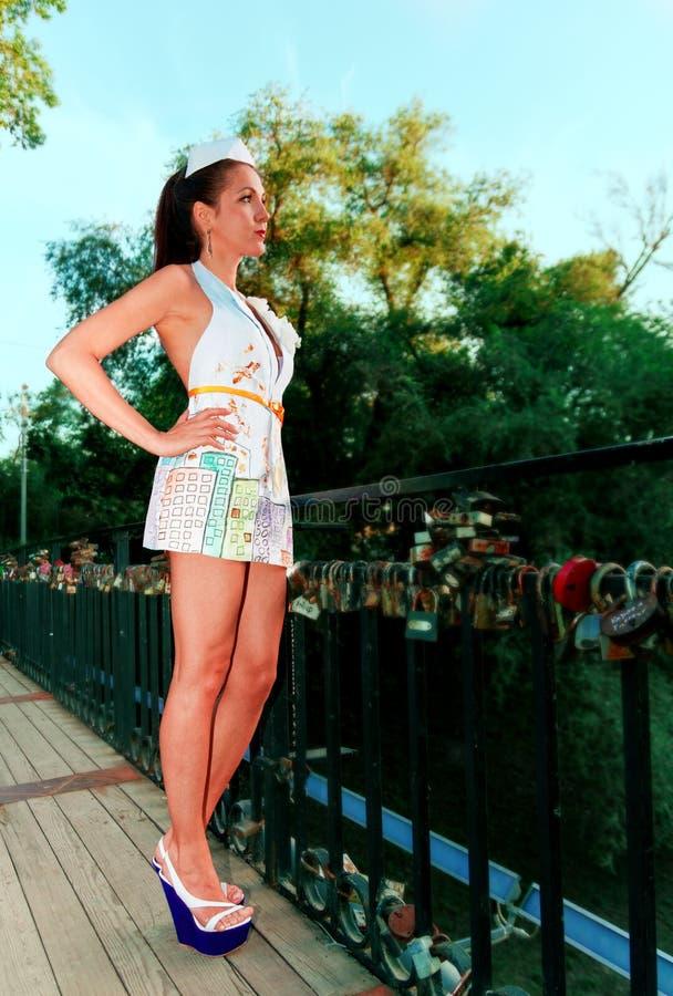 性感女孩在全长的桥梁站立在看一件时兴的纸的礼服直接 免版税图库摄影