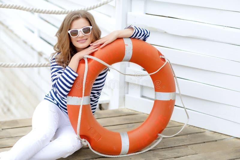 性感女孩对以水手的形式木墙壁有保险索和盖帽的 射击在白色的演播室 免版税库存图片