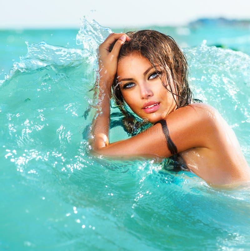 性感式样女孩游泳和摆在 免版税库存照片