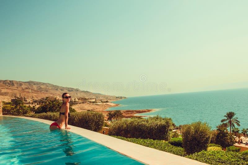性感无忧无虑式样放松在豪华无限游泳池 少妇休息在温泉渡假胜地 夏天豪华假期 旅游业 库存照片