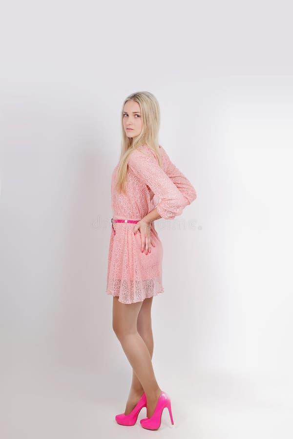 年轻性感白肤金发在桃红色礼服 工作室 垂直 免版税库存照片