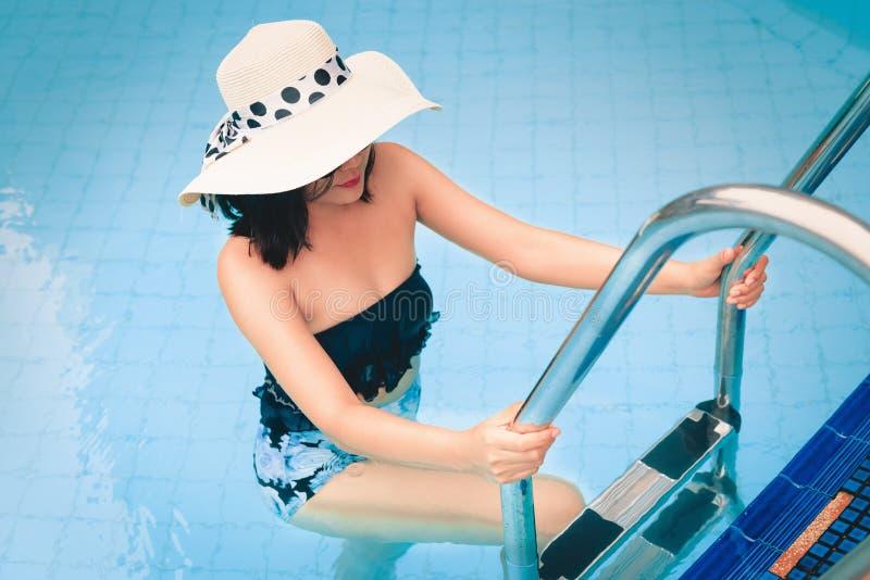 性感的亚洲妇女步,假日画象在水池梯子的和 库存图片
