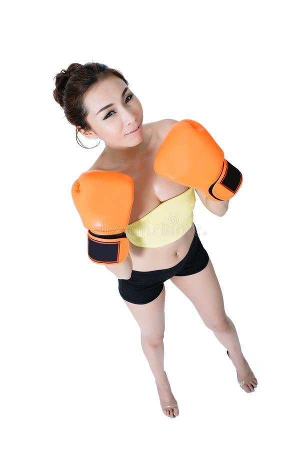 性感的亚裔少妇减肥佩带在wh的适合橙色露指手套拳击 免版税图库摄影