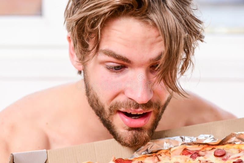 性感的人吃说谎在床上的比萨 在家是在一栋明亮的公寓的床上吃一鲜美比萨的学生 有胡子的人 图库摄影