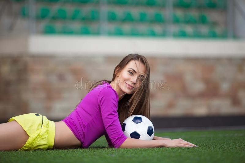 性感的健身妇女或啦啦队员有足球的 库存照片