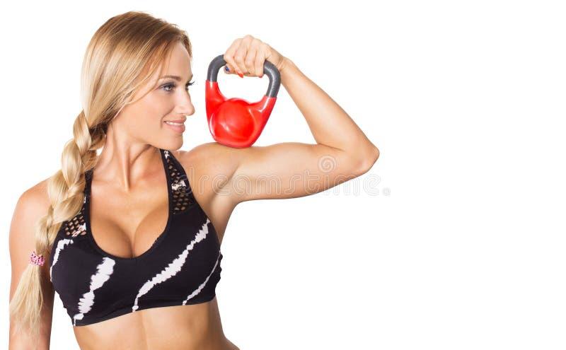 年轻性感的健身式样藏品红色kettlebell 免版税库存图片