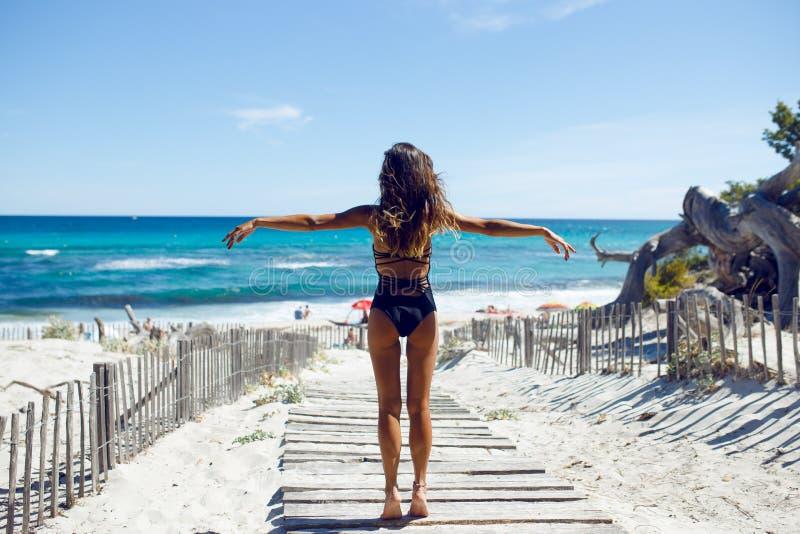 性感的在海滩的妇女佩带的比基尼泳装 站立在海滨的泳装的年轻女性用她的手上升了 库存照片