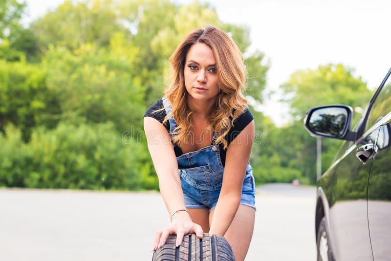 性感的在路旁的妇女变速轮 免版税库存图片