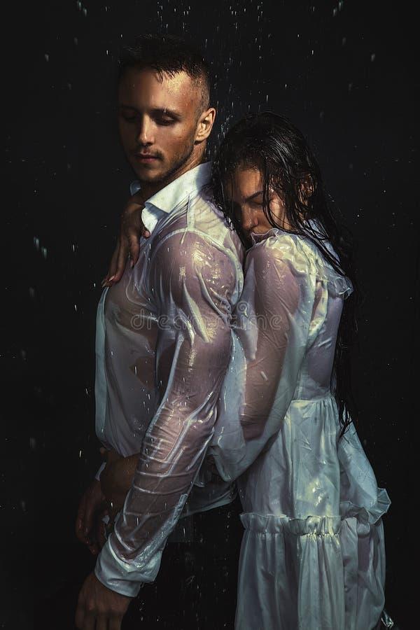性感的夫妇画象在白色衬衫和礼服身分的在雨下 图库摄影