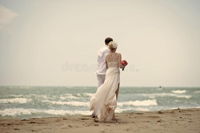 性感的夫妇 在海滩的走的婚礼夫妇 免版税图库摄影