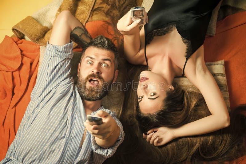 性感的夫妇 在爱手表电视的夫妇 库存照片