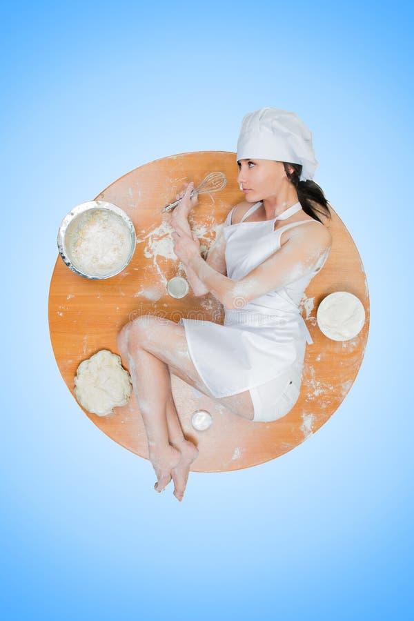 性感的女孩佩带的厨师准备面团 免版税库存图片