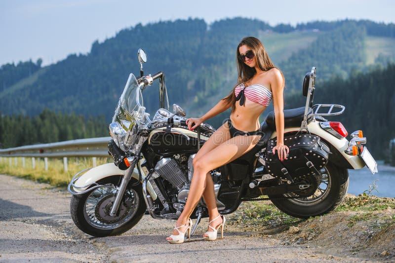 年轻性感的女孩坐定制的巡洋舰摩托车 免版税库存图片