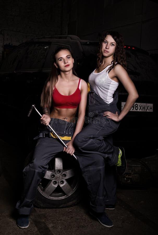 性感的女孩技工坐轮胎在他的手上的拿着一把板钳在汽车修理 无色的生活概念 免版税库存图片