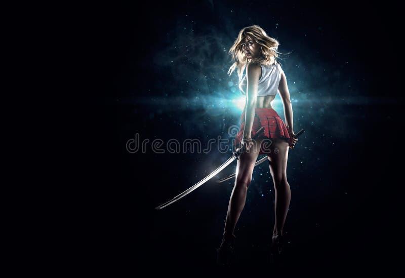 年轻性感的女孩站立与剑 库存图片