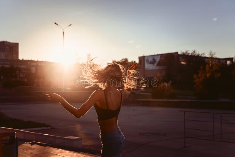 性感的女孩跳舞在日落的城市 库存照片