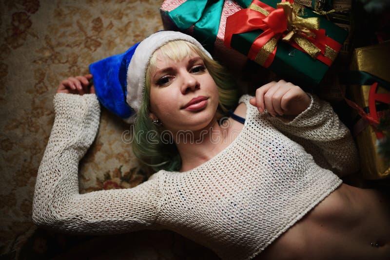 性感的女孩画象说谎在与礼物的圣诞树下 免版税库存图片