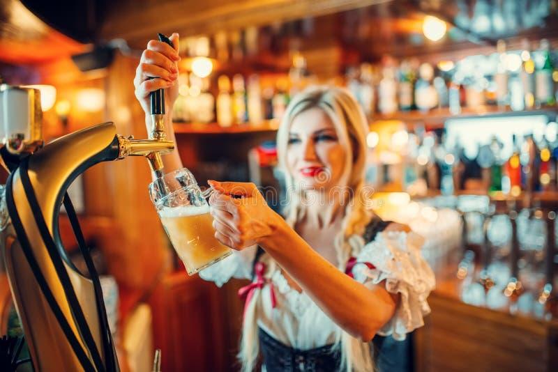 性感的女服务员倒啤酒入杯子在counte 免版税库存照片