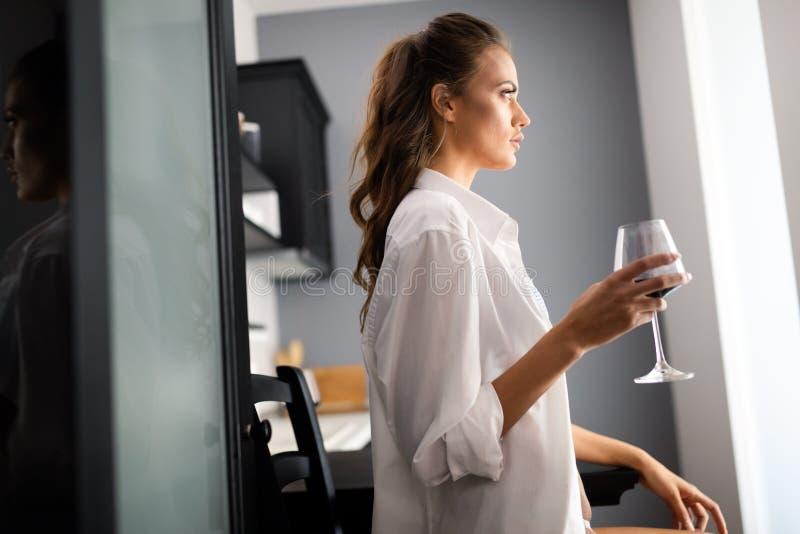 性感的女用贴身内衣裤的美丽的引诱的年轻女人有一杯的酒 免版税库存图片