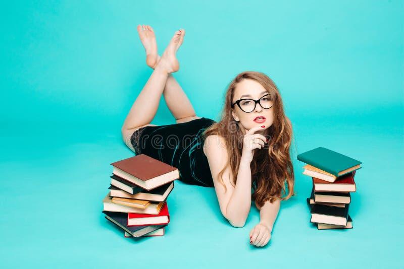 性感的女老师看书使打手势惊奇 免版税库存照片