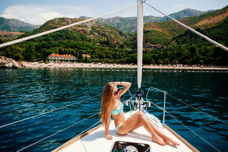 性感的妇女在游艇放松在海 免版税图库摄影
