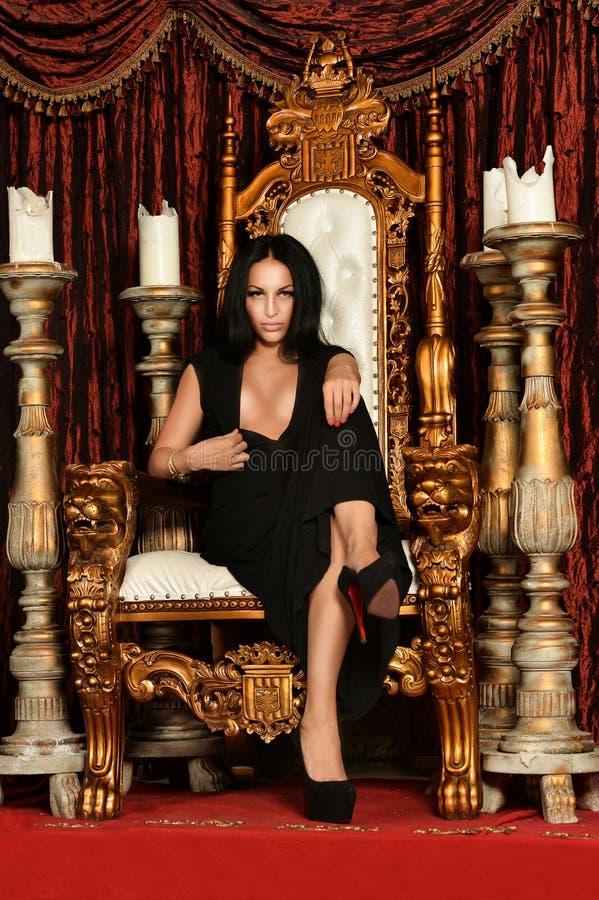性感的妇女坐王位 免版税库存照片