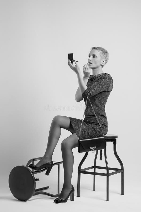 性感的妇女坐高凳并且绘嘴唇 免版税库存照片