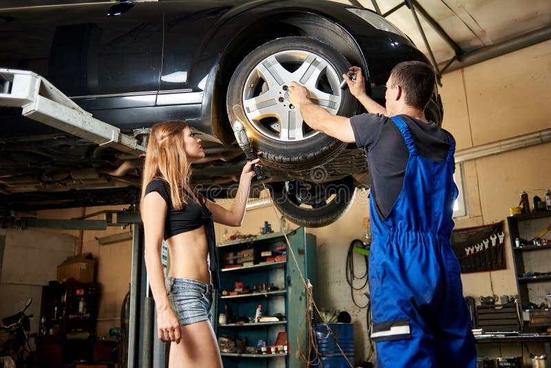性感的妇女帮助汽车机械师在液压悬挂的修理汽车 免版税图库摄影