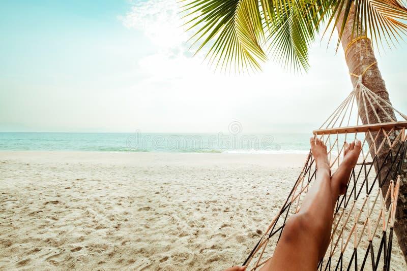 性感的妇女的美好的被晒黑的腿 放松在吊床在含沙热带海滩 免版税库存图片