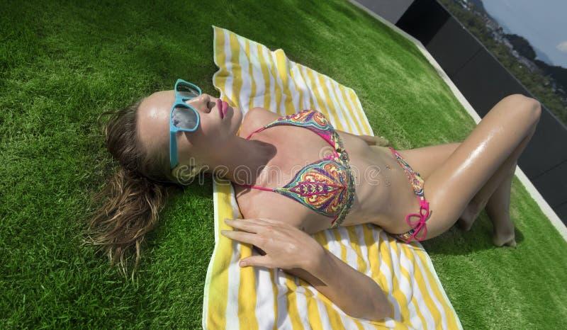 性感的妇女顶视图说谎在绿草背景的镶边海滩毛巾的比基尼泳装和蓝色太阳镜的 免版税图库摄影