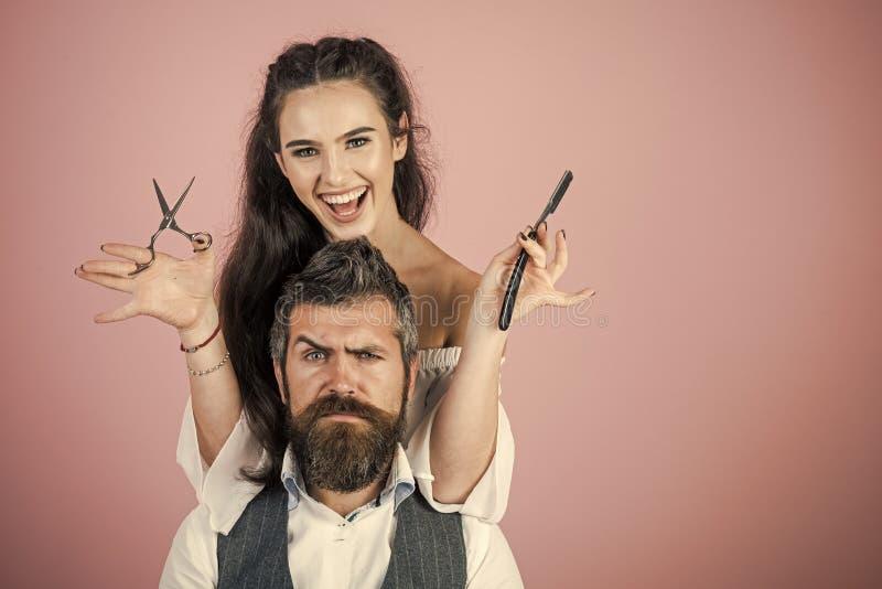 性感的妇女 有剃刀的,剪刀妇女剪了人的头发 库存图片