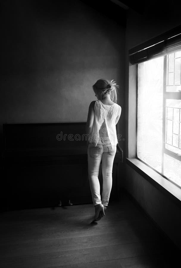 性感的妇女黑白画象在窗口前面的 免版税库存照片