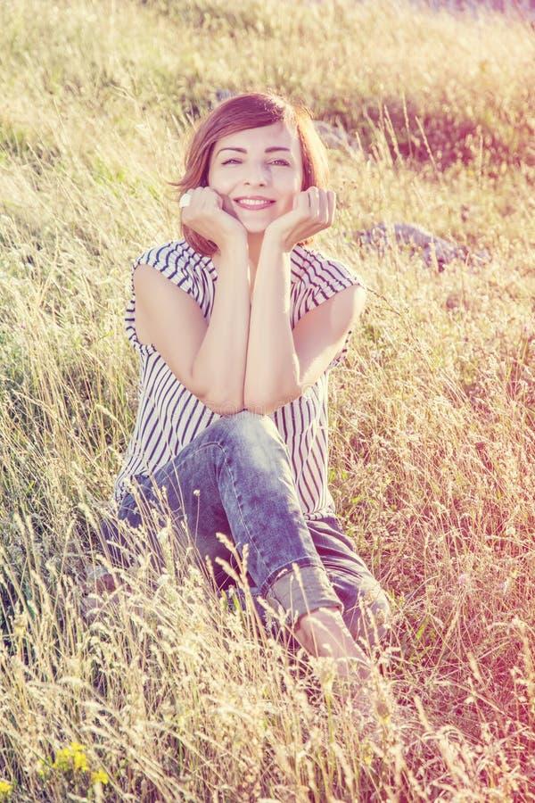 性感的少妇在草甸,彩虹过滤器 免版税库存照片