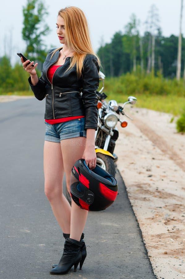 性感的少妇谈话在一个手机,当拿着摩托车盔甲时 库存图片