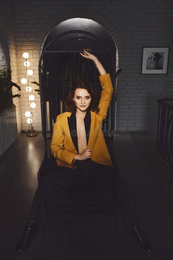 性感的年轻女人在赤裸身体的黄色燃烧物的和时髦方格的裤子的坐金属椅子和摆在 免版税库存照片