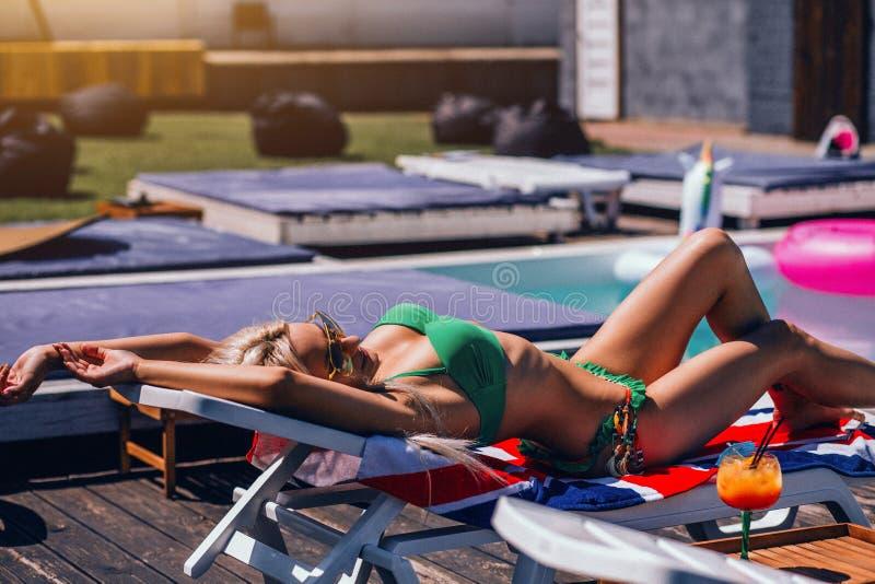 性感的年轻女人有在轻便折叠躺椅的Sunbath在游泳场附近在绿色比基尼泳装 免版税库存照片