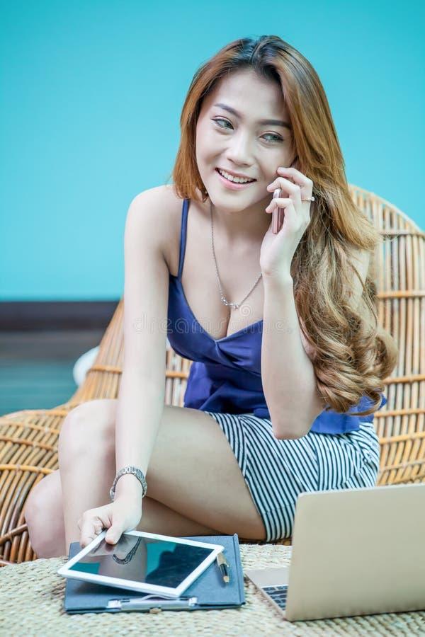 性感的年轻女实业家谈话在手机和微笑 免版税图库摄影