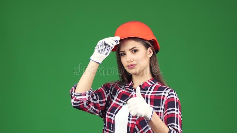 性感的幼小母显示赞许的承包商佩带的安全帽 免版税库存图片