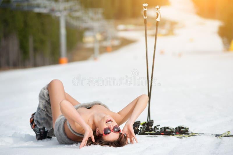 性感的微笑的女性滑雪者在多雪的倾斜说谎在滑雪电缆车下 库存图片