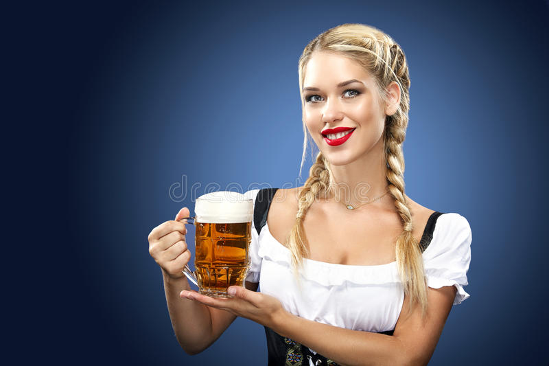 年轻性感的慕尼黑啤酒节女服务员,穿一件传统巴法力亚礼服,在蓝色背景的服务的大啤酒杯 免版税库存照片