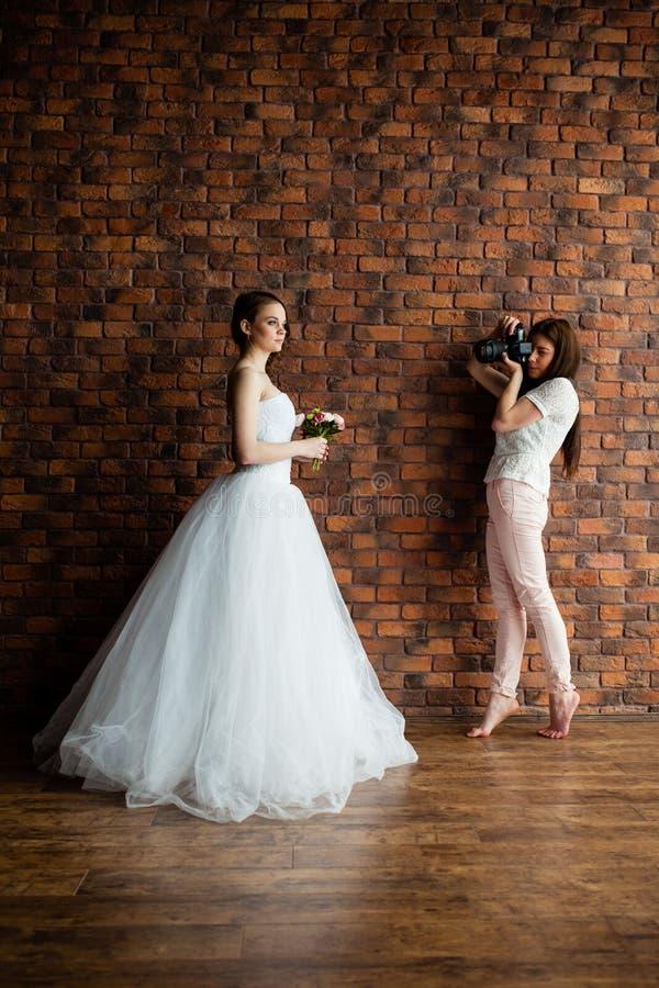年轻性感的摄影师在演播室采取图片新娘 免版税库存图片