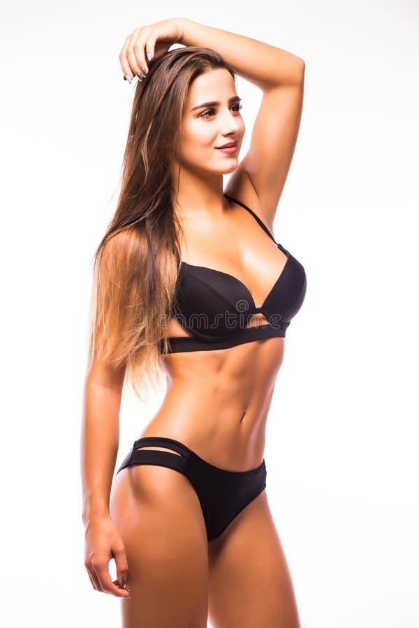 性感的摆在白色背景的妇女佩带的海军黑游泳衣 库存照片